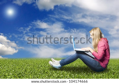 teenager girl in a meadow with her laptop chatting online