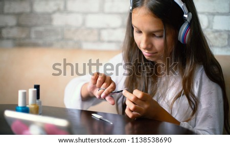 Teenager girl in headphones chatting online on phone making manicure cutting nails with scissors with free copy space at home. Beauty, bodycare, wellness, hygiene, communication, leisure time concept. #1138538690