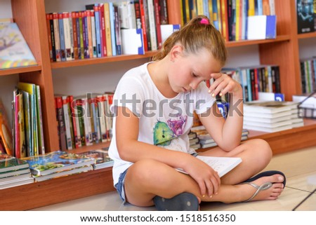 Teenager girl in library in front of books. Cute young child sitting on floor and reading book. Little kid reads in a bookstore, surrounded by colorful books. Library, Shop, Shelving In Home.