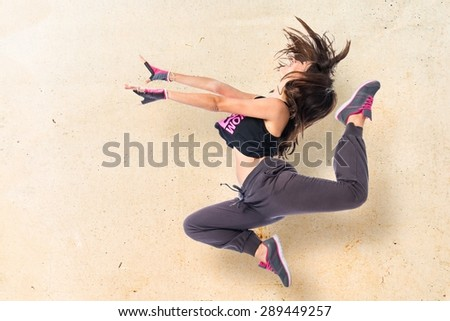 Teenager girl jumping in hip hop style over textured background