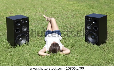 teenager girl listening to classical music on the lawn - stock photo