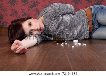 Teenager girl lying on the floor at home after an overdose of pills. Her eyes are open and there is a bottle of pills on the floor beside her.