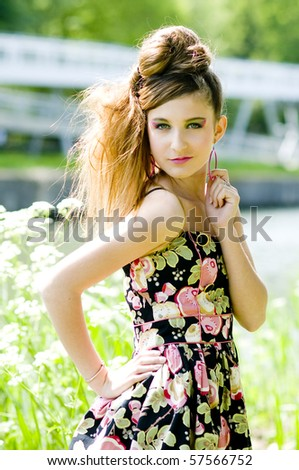Teenager girl model presenting clothes in the park near the water and a bridge