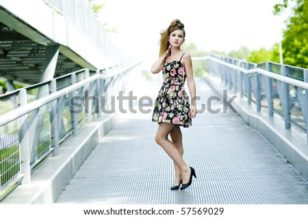 Teenager girl model presenting clothes on a bridge in the parc, light natural background