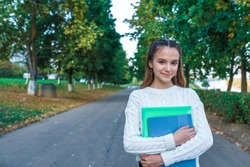 teenager girl of 11-14 years old, in summer in city park in fall, smiling happily, resting after school and college lessons, notebooks folders textbooks in her hands. Free space for text