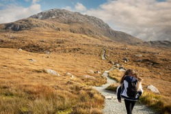 Teenager girl on a path to a mountain peak, Diamond hill in Connemara National park, county Galway, Ireland, Bright sunny day, blue cloudy sky. Hiking and outdoor activity.  Popular tourist spot.