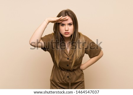 Teenager girl over isolated background looking far away with hand to look something