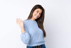 Teenager girl over isolated white background saluting with hand with happy expression