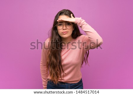 Teenager girl over purple wall looking far away with hand to look something
