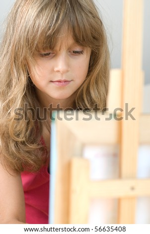teenager girl painter with easel - stock photo