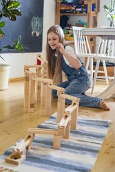 Teenager girl playing track constructor block tower with metallic ball Maria Montessori materials for kids development. Female child use self educational eco friendly playthings for logical mindset