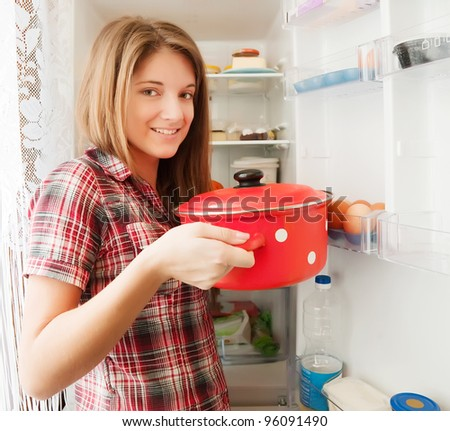 Teenager girl putting pan into refrigerator  at home