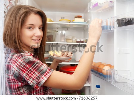 Teenager girl putting snack into refrigerator  at home