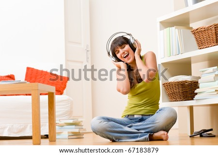 Teenager girl relax home - happy listen to music with headphones singing