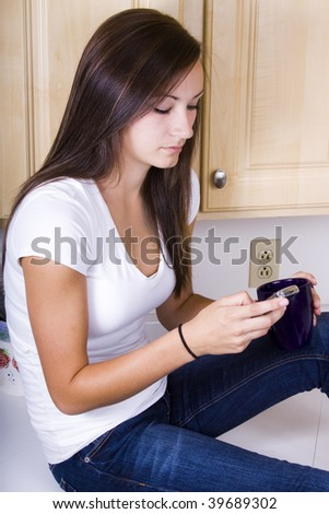Teenager Girl Sitting in the Kitchen Texting