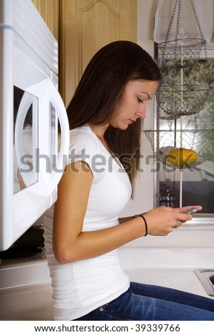 Teenager Girl Sitting in the Kithcen Texting