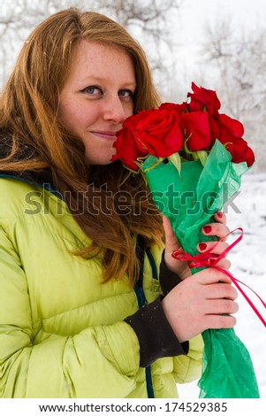 Teenager girl smelling red roses on the Valentines Day.