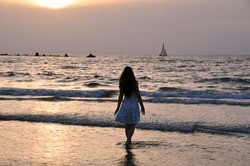 Teenager girl standing in a sea edge at sunset time