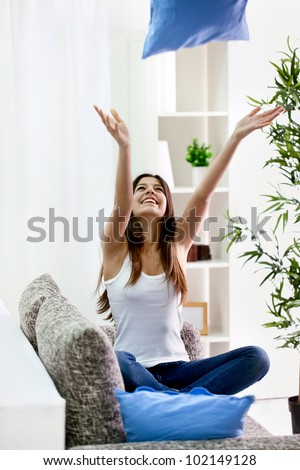 Teenager girl throwing  pillow into the air, having fun