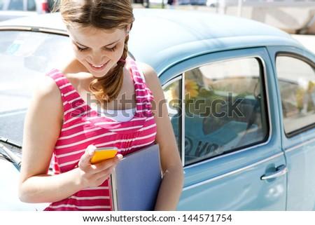 Teenager girl using her cell phone and writing a message on her smartphone leaning on a classic blue car in the city during a sunny day, smiling.