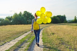 Teenager girl with backpack and yellow balloons running on country road, rear view. Happy girl walking forward, sky in the clouds, meadow, nature background