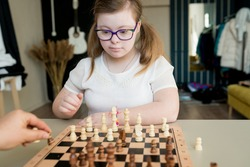 Teenager girl with Down syndrome playing chess on the game board. Disabled kids examining chessboard at home. Development of capacity children