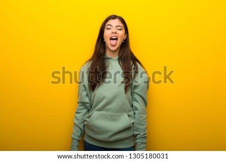Teenager girl with green sweatshirt on yellow background showing tongue at the camera having funny look