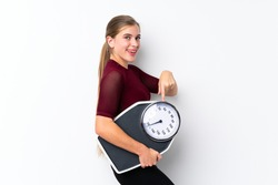 Teenager girl with weighing machine over isolated white background holding a weighing machine and pointing it