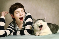 teenager handsome boy in striped blouse and siberian cat close up portrait yawn synchronized together