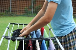Teenager hanging clothes on drying rack as a chore
