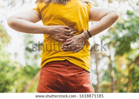 Teenager having a back pain - Person suffering from backache - Woman massaging her spine or muscle because of ache