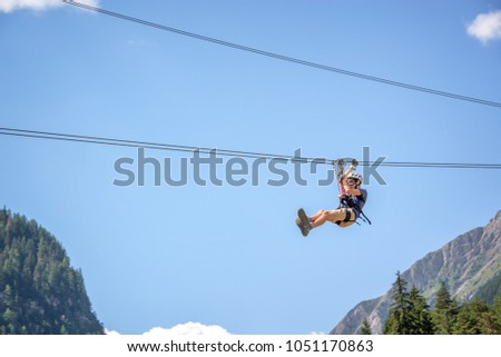 Teenager having fun on a zip line in the Alps, adventure, climbing, via ferrata during active vacations in summer