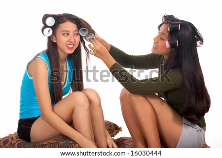 teenager helping her friend removing her hair rollers
