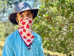 Teenager hikes in the park and covers his face with a bandana mask with red stars. Summer, green trees background. The boy is wear a cloth face covering to help prevent the spread of COVID-19