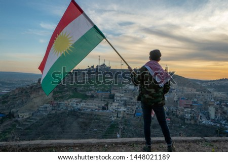 Teenager holding the Kurdistan flag in northern Iraq at sunset time on Nowruz 2019