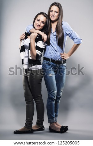 teenager hugging her sister on gray background