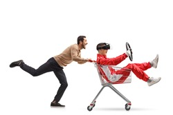 Teenager in a racing suit with VR googles in a shopping cart being pushed by a young man isolated on white background