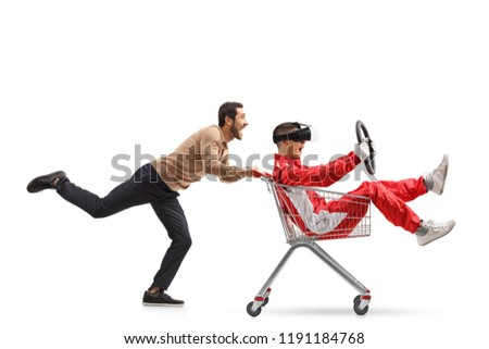 Teenager in a racing suit with VR googles in a shopping cart being pushed by a young man isolated on white background #1191184768