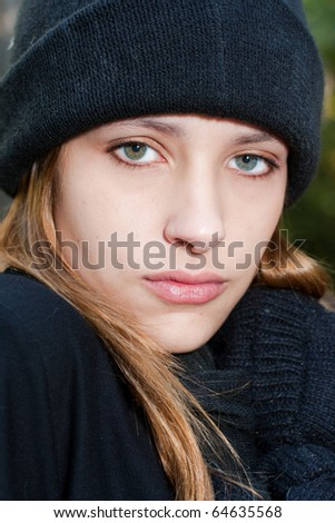 teenager looking at camera wearing winter mittens, scarf and hat