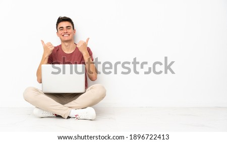 Teenager man sitting on the flor with his laptop with thumbs up gesture and smiling Foto stock ©
