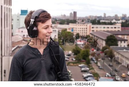 teenager on the roof of the house listens to music #458346472
