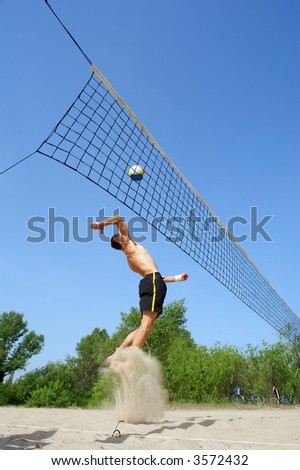 Teenager playing beach volleyball - jumps high with beautiful splash of sand. Shot near Dnieper river, Ukraine.