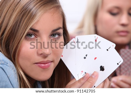 Teenager playing cards holding four aces