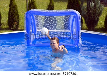Teenager playing water polo in garden pool.