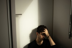 Teenager portrait under a door sad taking is head hand alone