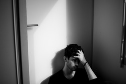 Teenager portrait under a door sad taking is head hand alone black and white