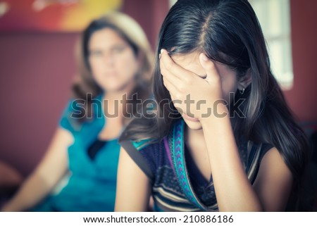 Teenager problems - Teenage girl cries while her mother looks at her on the background