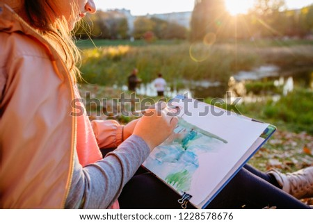 Teenager school girl drawing beautiful picture outdoor in the park at sunset. Open air activity for school age children concept. Close up