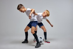 teenager school kids playing football in studio, practice dribbling skills, children in sportswear hold competition