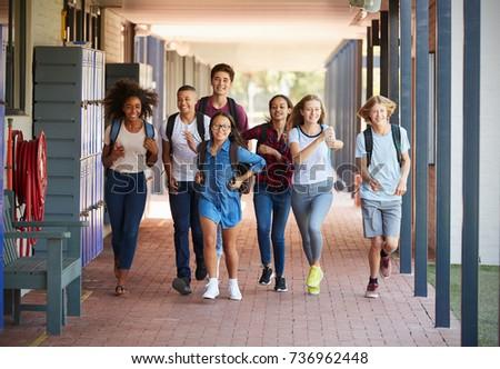 Teenager school kids running in high school hallway